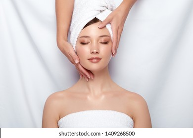 beauty master holding woman's face that lying down on white, head and face treatment for women, client of spa theraphy