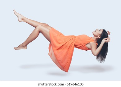 Beauty in mid-air. Full length studio shot of attractive young woman in orange dress hovering in air and looking surprised