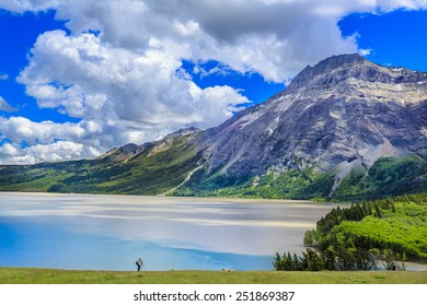 The beauty of Middle Waterton Lake from the hotel at Waterton Lakes National Park in Alberta, Canada.  A photographer gives you the scale of the landscape.
