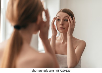 Beauty in mirror reflection. Over the shoulder view of beautiful woman touching her face while looking in the mirror