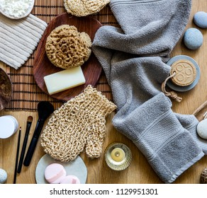 beauty mix of traditional and zen body care objects for genuine shower or bath with natural sponge, loofah, towel, solid soap and makeup brushes, top view