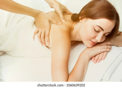 Beauty model with back neck pain massage at spa warm tone