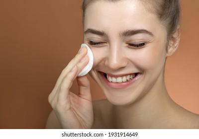Schönheitsmodell, das ihre perfekte Haut mit Baumwollpolster-Schwamm reinigt, Nahaufnahme. Junge Frau interessiert sich für ihr Gesicht. Spa und Wellness, Hautpflegekonzept. Nahaufnahme.