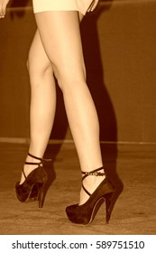 Beauty model dressed in black high heels in purple carpet, closeup of photo