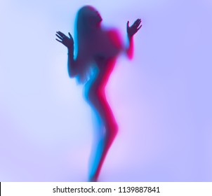Beauty Model girl dancing silhouette. Beautiful sexy young woman with perfect slim body dance in uv light. Seduction. Disco