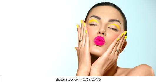 Beauty-Model-Mädchen mit Mode-Make-up, Hellgelbe Augenlinie und Nägel, trendige Maniküre. Auge macht kreative Ideen aus. Sommerschminken. Küss Geste. Schöne junge Frau Porträt. Gesichtshaut, Nahaufnahme