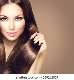 Beauty Model girl with Healthy Brown Hair. Beautiful brunette woman touching her long smooth shiny straight hair. Hairstyle. Hair cosmetics, haircare. Hair care, extensions. Brown background
