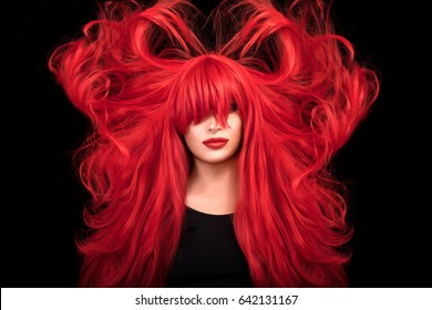 Beauty model girl with healthy long red hair and straight bangs covering eyes, with red lipstick and bright makeup. Hair color beauty concept. Flying long hair. Portrait isolated on black background