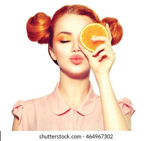 Beauty Model Girl holding Juicy Orange slice. Beautiful Joyful teen girl with freckles, funny red hairstyle and yellow makeup. Professional make up. Isolated on white background