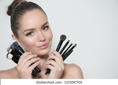 4dc5a180212 Beauty model girl, makeup artist holding set of make up brushes and  smiling. Beautiful