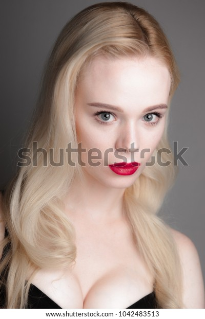 Beauty model girl with perfect make-up red lips and blue eyes looking at camera. Portrait of attractive young woman with blond hair. Beautiful female face with clear fresh skin. Fashion close up shot.