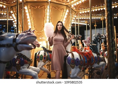 Beauty model girl riding the horse carousel with retro lights and eating cotton candy in amusement park