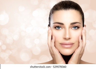 Beauty model girl with a smooth unblemished complexion, perfect skin with no makeup makeup and hands on cheeks with a serene expression in a skincare and spa concept. Closeup over bokeh background