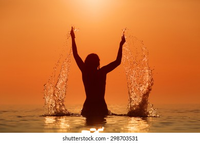 Beauty Model Girl Splashing Water with her hands. Teen girl Swimming and splashing on summer beach over sunset. Beautiful Woman in Water