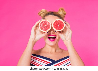 Beauty Model Girl takes Juicy Grapefruit. Beautiful Joyful young girl, funny blonde hairstyle and pink makeup.Holding Orange Slices and laughing, emotions.