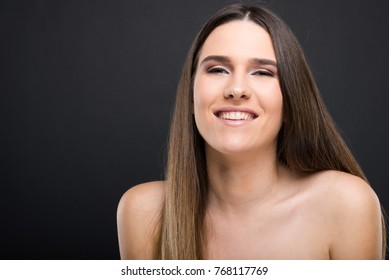 Beauty model with gorgeous sking and straight hair looking at camera and smiling on dark background