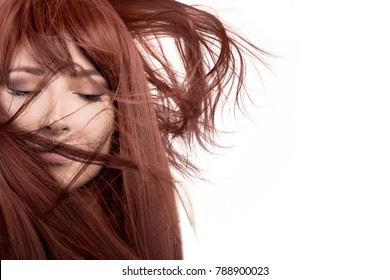 Beauty model with healthy long red hair blowing over her face wearing subtle eye makeup in a close up isolated beauty portrait with copy space