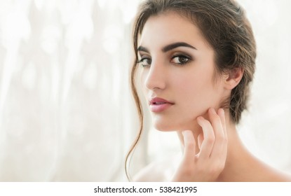 Beauty model with  make up and fresh skin is posing front of the window. Youth and Skin Care Concept.  Make up and Hair.  Close up, selected focus.