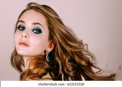 Beauty model makeup green smoky face close up pink background