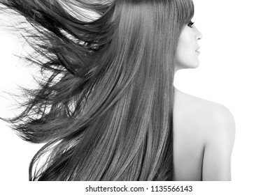Beauty model with naked shoulders and gorgeous long hair blowing to the side isolated over white in a monochrome beauty portrait viewed from the rear. Healthy hair. Haircare products