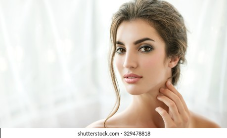 Beauty model with  natural make up, wet hair and fresh skin is posing front of the window. Youth and Skin Care Concept.  Make up and Hair. Morning.  Close up, selected focus.