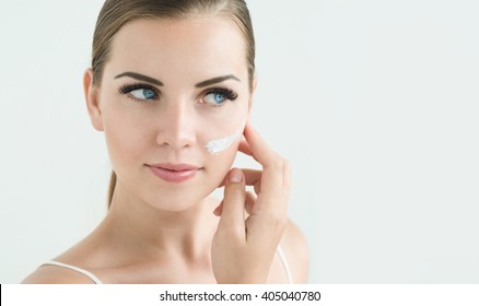 Beauty Model with  Perfect Fresh Skin and Long Eyelashes  applying Face Cream. Youth and Skin Care Concept. Spa and Wellness. Make up and Hair. Lashes. Close up, selected focus.