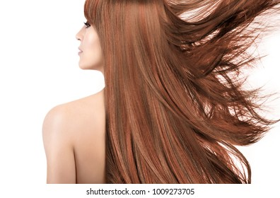 Beauty model with a smooth unblemished skin, naked shoulders and gorgeous long coppery hair with highlights blowing to the side isolated over white in a beauty portrait viewed from the rear