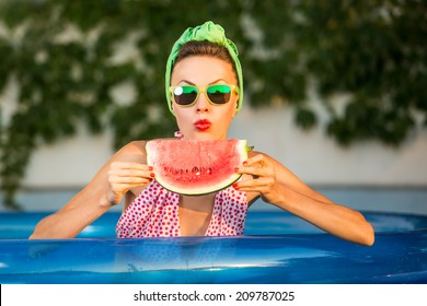 Beauty model with watermelon enjoy her vacation in swimming pool