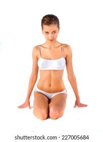 Beauty model in white lingerie sitting on the floor.