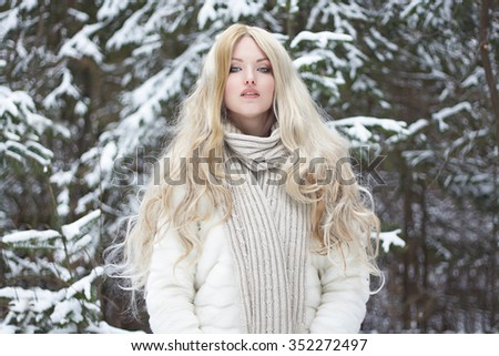 bfa36eabc Beauty model in winter forest. beautiful young Woman in fashionable Fur  Coat and scarf.