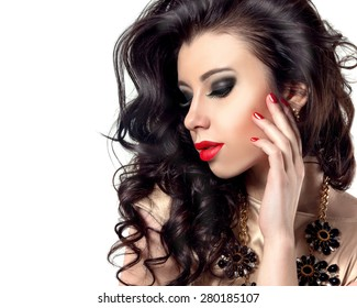 Beauty Model Woman with Long Black Curly Hair. Healthy Hair and Beautiful Professional Makeup. Red Sexy Lips and Smoky Eyes Make up with False Lashes. Gorgeous Glamour Lady Portrait. Red Manicure.
