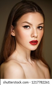 Beauty Model Woman with Long Brown Straight Hair. Healthy Hair and Beautiful Professional Makeup. Red Lips and black eyeliner Make up. Gorgeous Glamour Lady Portrait. Haircare, Skincare concept