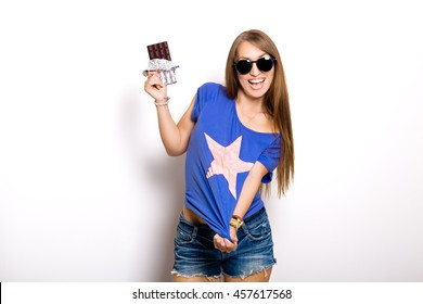 Beauty model woman in sunglasses eating dark chocolate. Beautiful Surprised young woman takes chocolate sweets,smiling and having fun. Funny girl, professional make up and bow hairstyle, pink