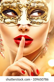Beauty model woman wearing venetian masquerade carnival mask at party over holiday glowing gold background. Christmas and New Year celebration. Glamour lady with perfect make up and hairstyle