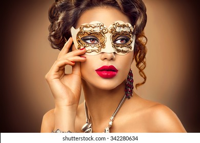 Beauty model woman wearing venetian masquerade carnival mask at party, over holiday background. Christmas and New Year celebration. Sexy girl with holiday makeup and manicure. Red lips and nails
