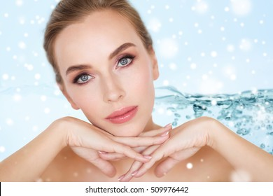 beauty, moisturizing, people and body care concept - close up of beautiful young woman face and hands over water splash bubbles on blue background and snow