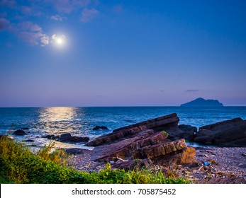 The beauty moment of moon nature and sea. The great supermoon is shining above the Pacific ocean. The moonlight is so strong, the light reflect to the sea in long and wide way toward the rocky shore.