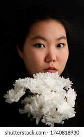 Beauty Mongolian fashion woman with white flowers. Glamour Asian woman on black background. Beautiful face make-up. Trends.