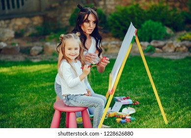 Beauty mother paint with her little daughter. Stylish woman drawing the picture with little girl. Cute kid in a white t-shirt and blue jeans