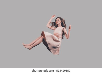 Beauty in motion. Studio shot of attractive young woman hovering in air