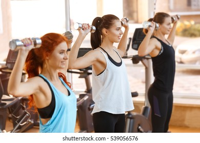 Beauty motivates. Shot of three attractive fitness females exercising together lifting weights at the gym smiling joyfully