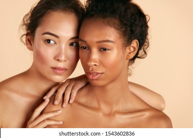 Beauty. Multi-ethnic women with natural face makeup and healthy skin portrait. Different ethnicity girls, beautiful asian and african models with glowing skin on beige background. Spa skin care