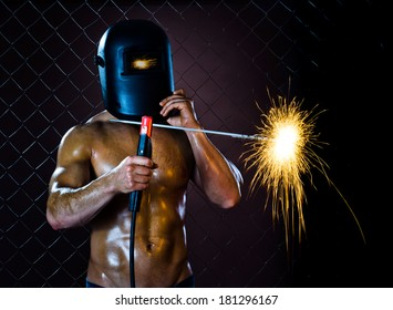the beauty muscular worker welder  man, weld  electric arc-weld, on netting fence background