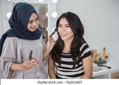 Beauty muslim make up artist applying cosmetic. Girl gets blush on the cheekbones