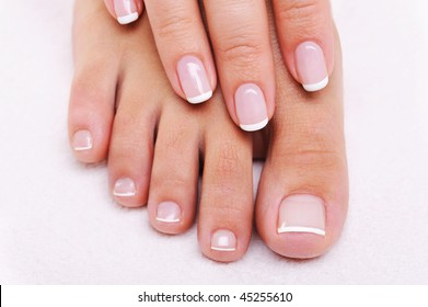 Beauty nails concept of a female hand and feet with beautiful french manicure and pedicure