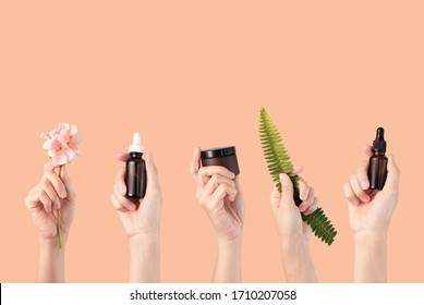 Schönheit natürliche kosmetische Hautpflegejar, Tropfer, Pumpflasche mit Bio-Blättern und Blumenzutat auf neutralem Hintergrund.