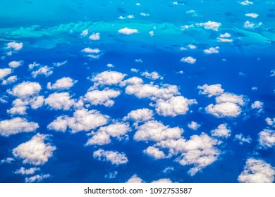 Beauty in nature. Aerial view of the clouds and blue sea.  Diverse blue tonalities. Point of view from an airplane arriving to Cuba
