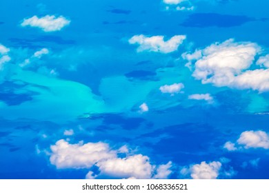 Beauty in nature in the Caribbean sea. Aerial view of the clouds and blue sea.  Diverse blue tonalities. Point of view from an airplane arriving to Cuba