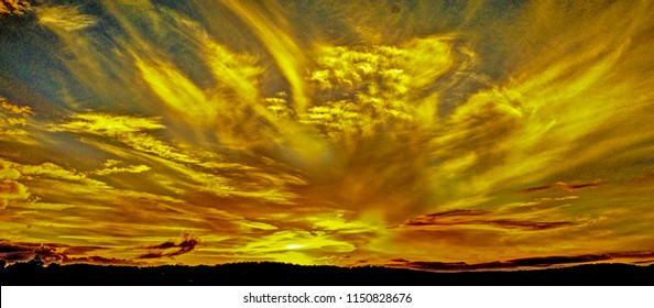 Beauty in nature. This tropospheric sky art photography is from the Australian East Coast.  Cirrus formation in an atmospheric pale steel blue sky. Sunset displays over water and through cloud.