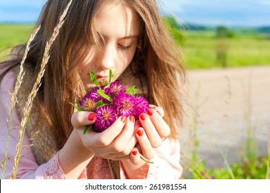Beauty of nature. Young beautiful girl smelling meadow clover flowers. Summertime outdoors.